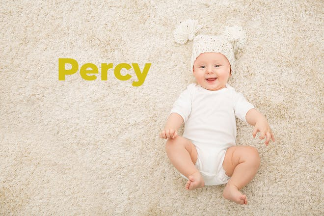 Baby lying on carpet with wooly hat on. Name Percy written in text