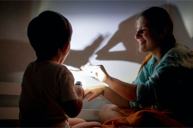 A toddler lights the bedroom wall with a torch while their mum raises her hand to make a shadow puppet