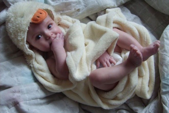 baby lying on bed in towel