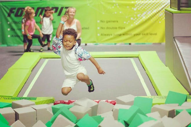 Young boy jumping off trampoline into foam pit