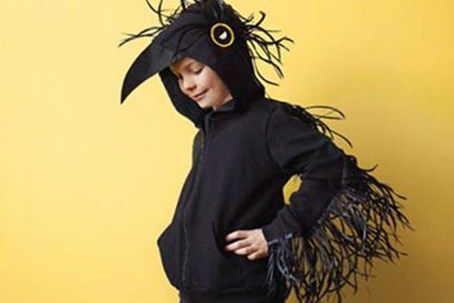 Boy dressed as a black crow