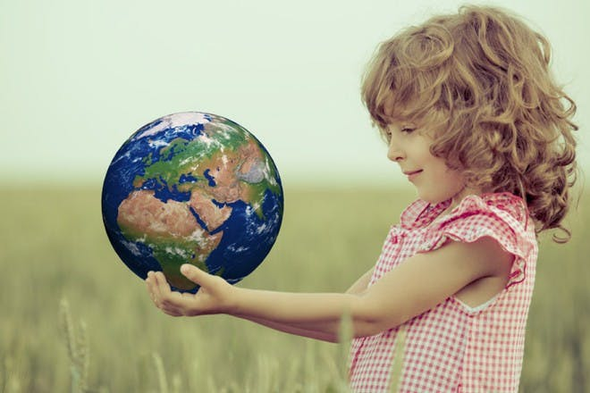 child holding the world in long grass