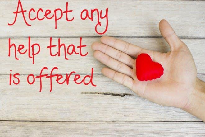 red heart in hand on wooden floor
