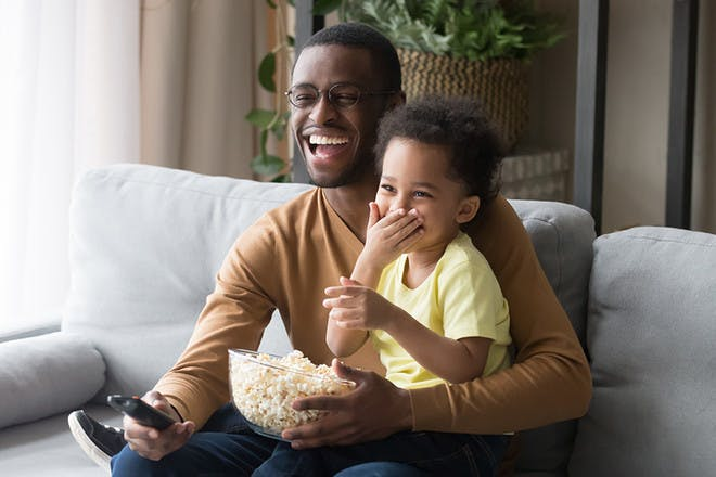 Dad and son watching a film with popcorn