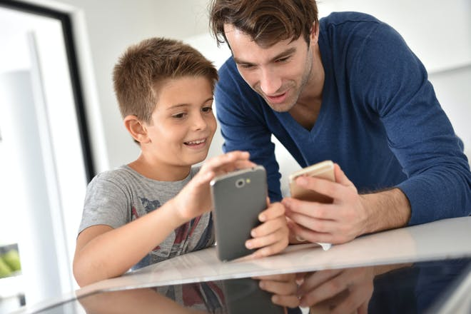 Father and 7 year old son using smartphone together in kitchen