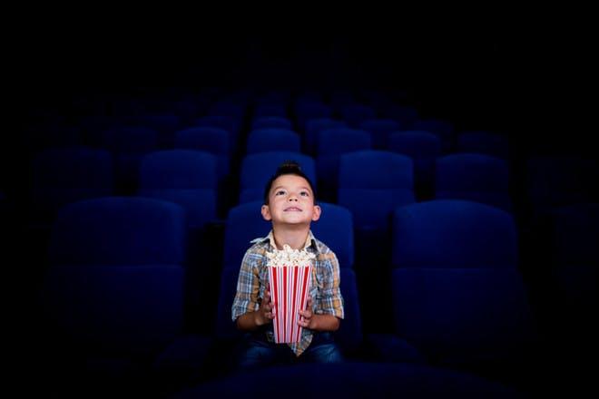 little boy sitting in cinema holding tub of popcorn