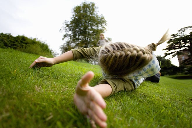 girl rolling down hill and holding out hand