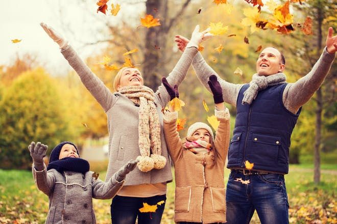 family happy in autumn leaves