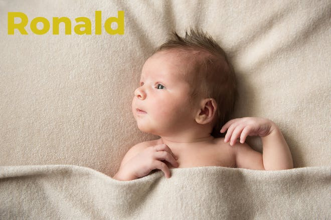 Baby lying in beige towel. Name Ronald written in text