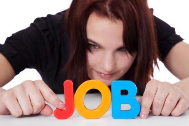 woman holding up colourful letters spelling 'job'
