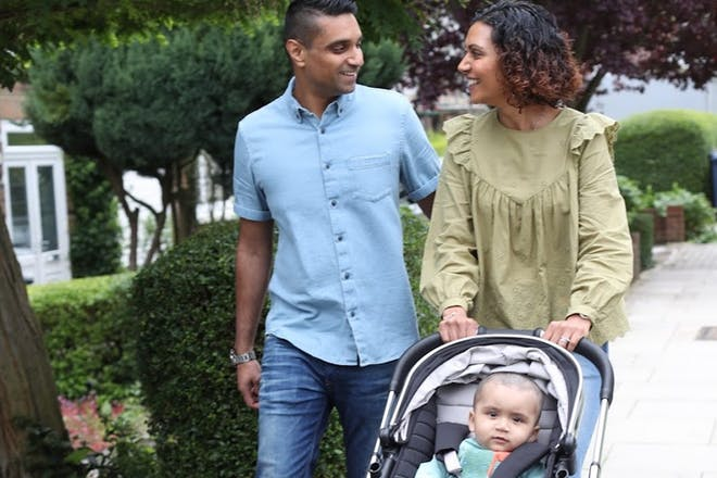 Couple walking with baby in pram