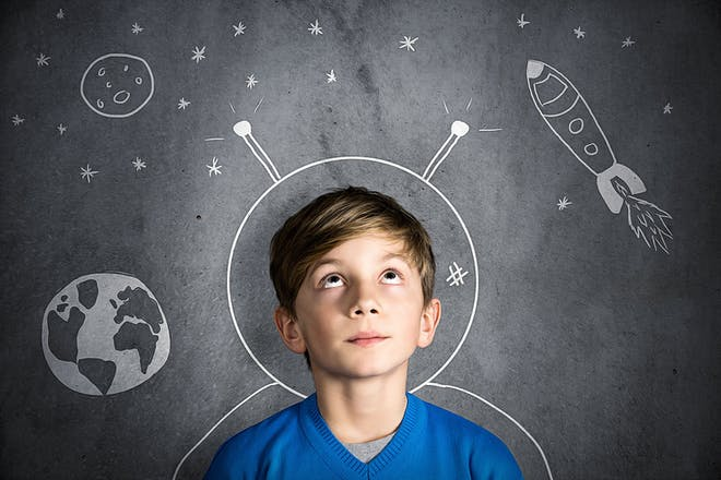 Boy standing against a blackboard with astronaut helmet and space drawn on it