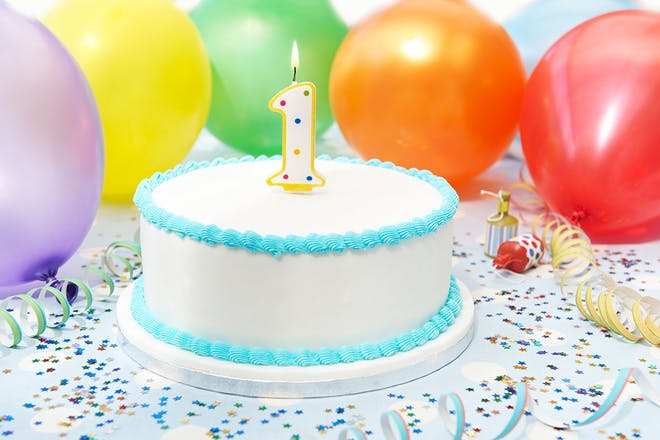 1-year-old birthday cake with balloons in the background