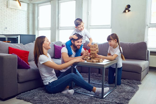 Family of mum, dad, boy and girl playing jenga at home in their living room