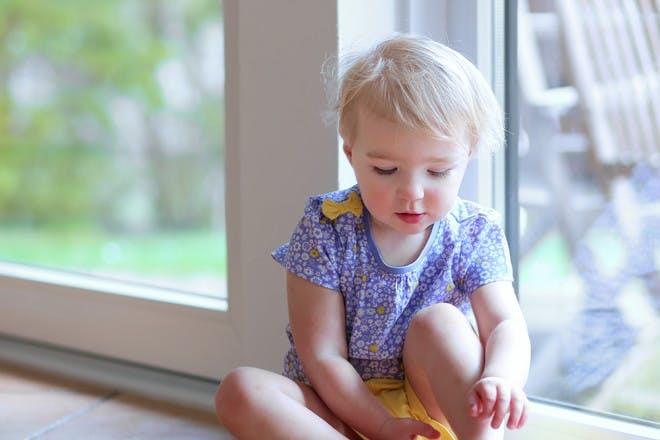 toddler sitting on floor putting shoe on