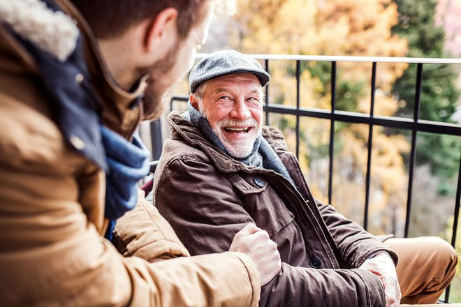 Older man and younger man laughing together outside
