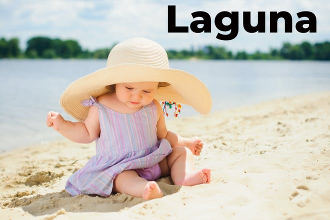 Baby girl on the beach with the word Laguna written in text