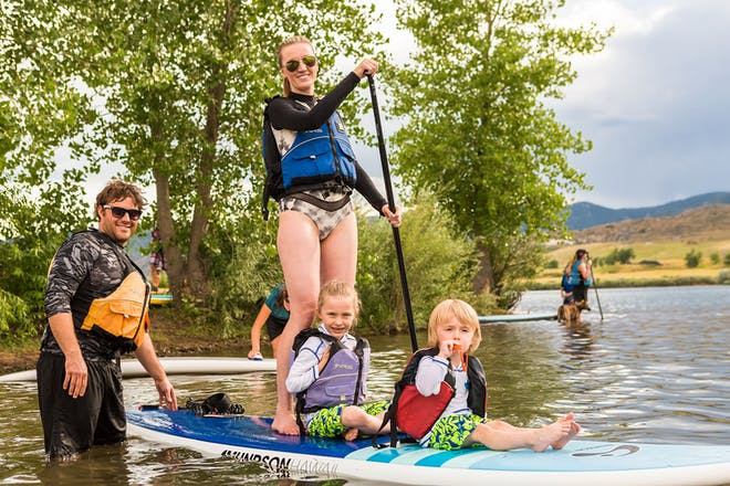 Mum and two children on stand up paddle board