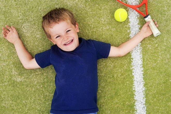 Boy lying on tennis court with racket and ball