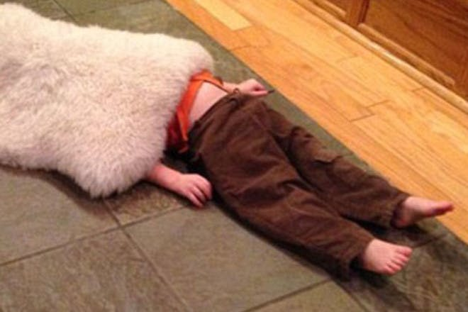 child hiding under rug