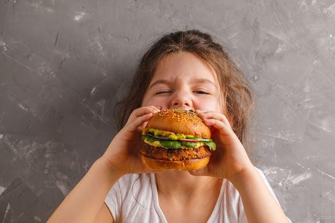 Little girl eating big veggie burger