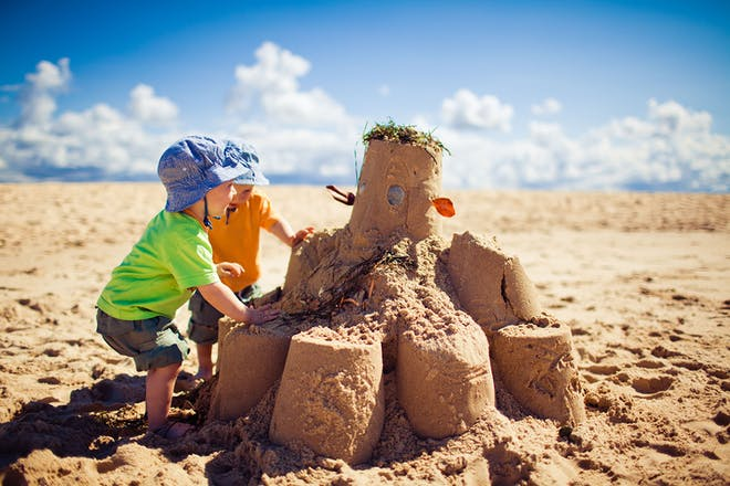 Two toddlers making huge sandcastle