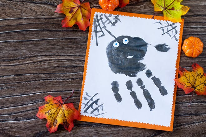 Picture of black spider made with painted handprint surrounded by autumn leaves for Halloween