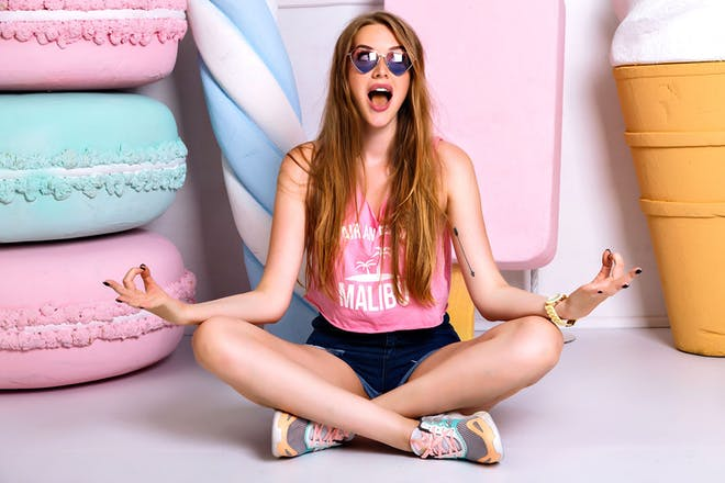 Young girl sitting in yoga pose on pastel-coloured background