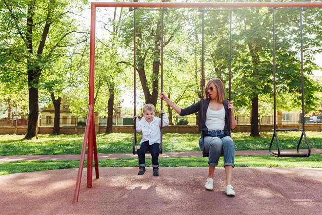 mum and boy sitting on swings in park