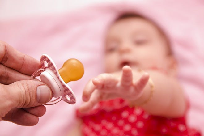 baby reaching for dummy