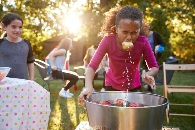 Little girl apple bobbing at a Halloween kids party