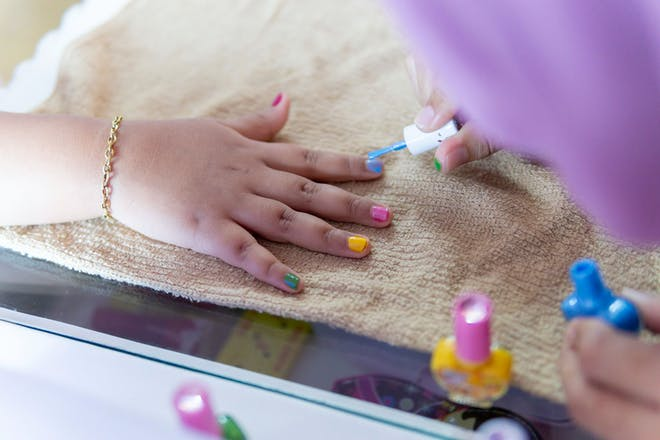A child getting their fingernails painted in bright colours
