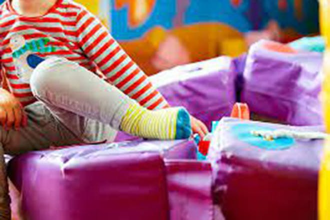 Child playing on soft play