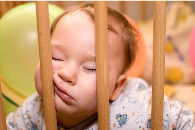 baby asleep on cot bars