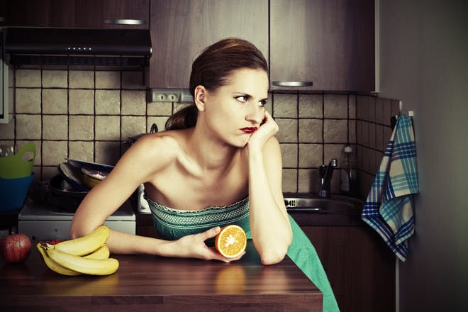 Woman looking bored in kitchen