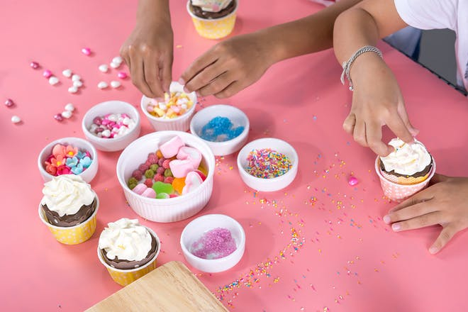 kids decorating cupcakes with bowls full of sweets and sprinkles