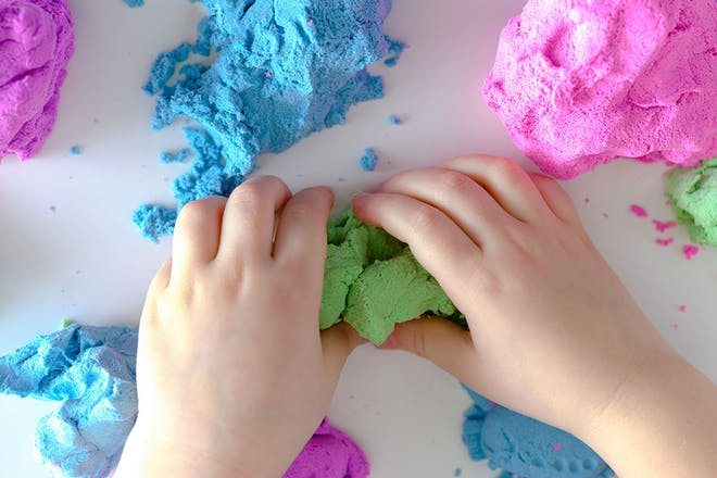 Child's hands playing with playdough