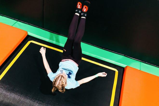 Girl jumping backwards onto trampoline
