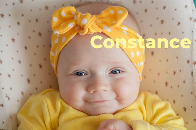 Baby wearing yellow headband. Name Constance written in text