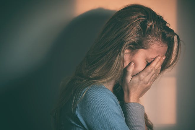 Depressed mum with hands over her face
