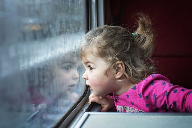 Little girl looking out of train window