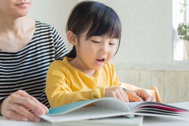 Mum reading a book with young girl