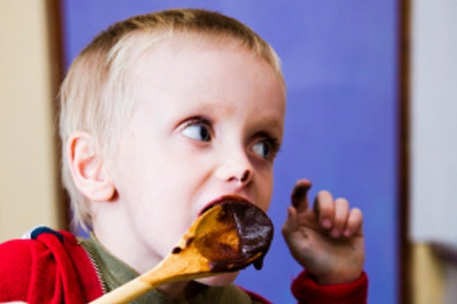 boy eating chocolate from wooden spoon