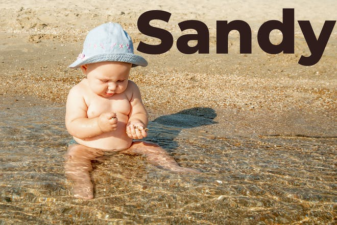 Baby in the sea with 'Sandy' written in text