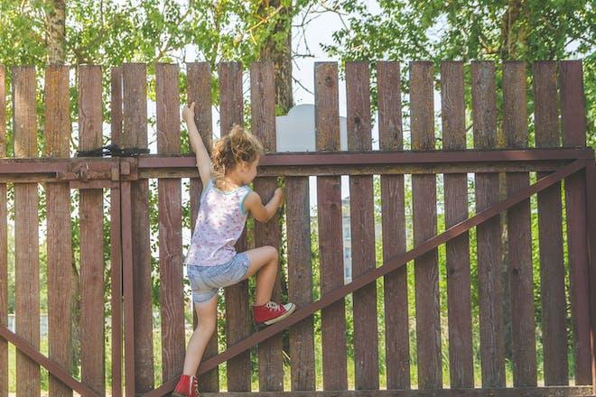 Girl climbing garden fence