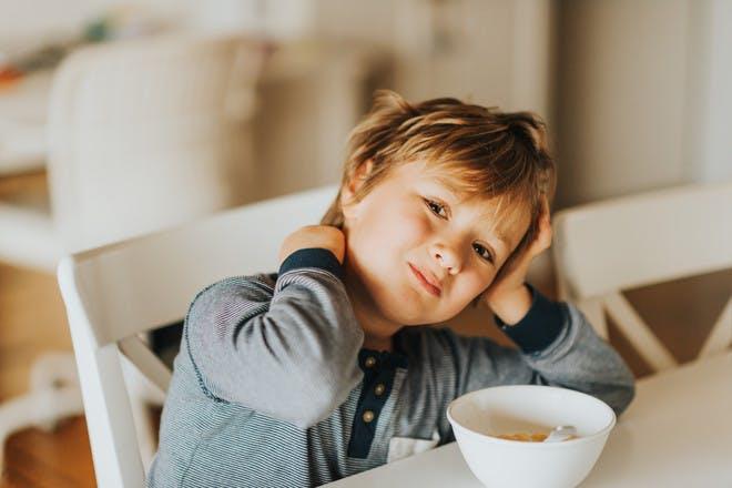 Child eating breakfast in pyjamas