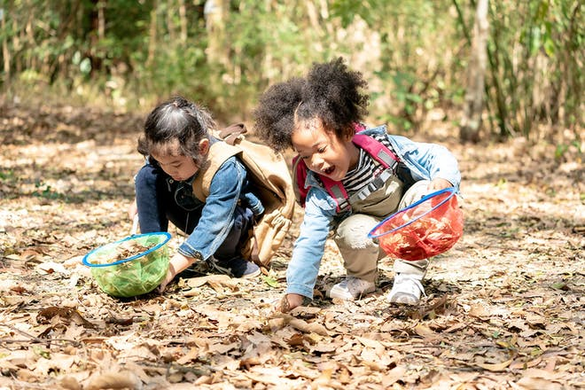two young girls collecting leaves outside