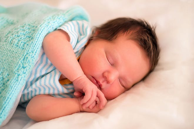 sleeping newborn with green blanket