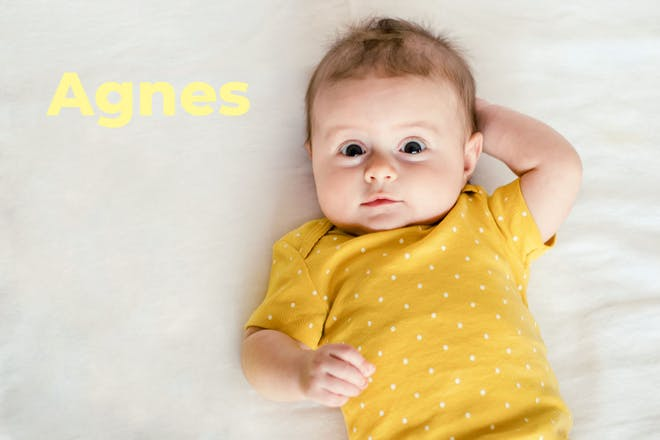 Baby wearing yellow baby grow. Name Agnes written in text