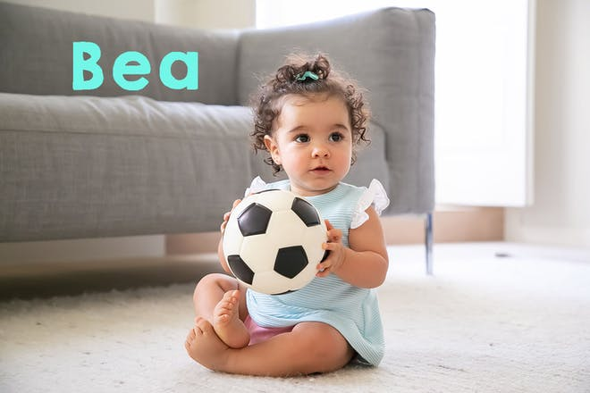 Baby girl holding a football. Text says Bea